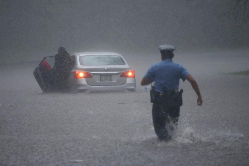 A Philadelphia police officer rushes to help a stranded motorist during Tropical Storm Isaias on Aug. 4. The storm spawned tornadoes and dumped rain during an inland march up the U.S. East Coast after making landfall as a hurricane along the North Carolina coast.