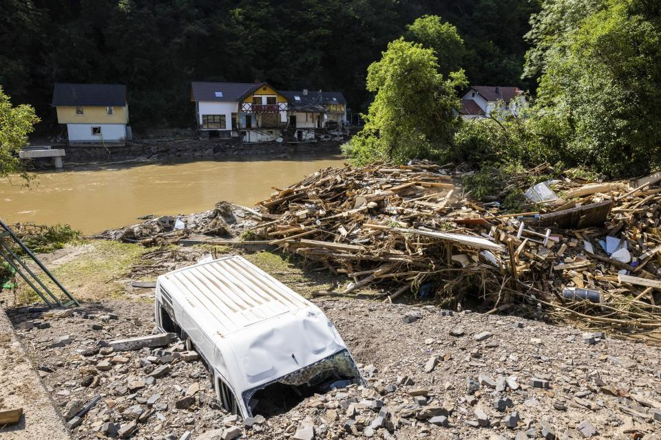 A van buried in debris and gravel on the banks of the river Ahr in Ahrbruck, Germany, Susnday July 18, 2021. Heavy rains caused mudslides and flooding in the western part of Germany. Multiple have died and are missing as severe flooding in Germany and Belgium turned streams and streets into raging, debris-filled torrents that swept away cars and toppled houses. (Philipp von Ditfurth/dpa via AP)