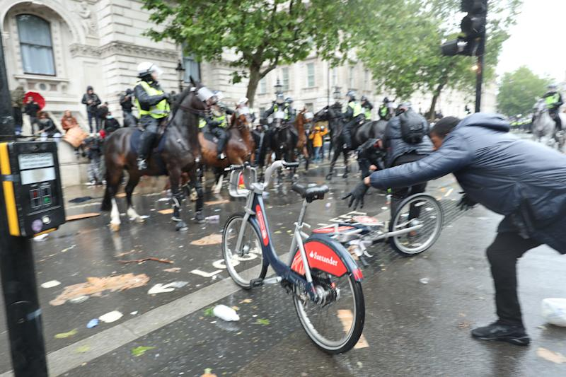 A bicycle is thrown at mounted police Police on horseback in Whitehall following a Black Lives Matter protest rally in Parliament Square, London, in memory of George Floyd who was killed on May 25 while in police custody in the US city of Minneapolis.