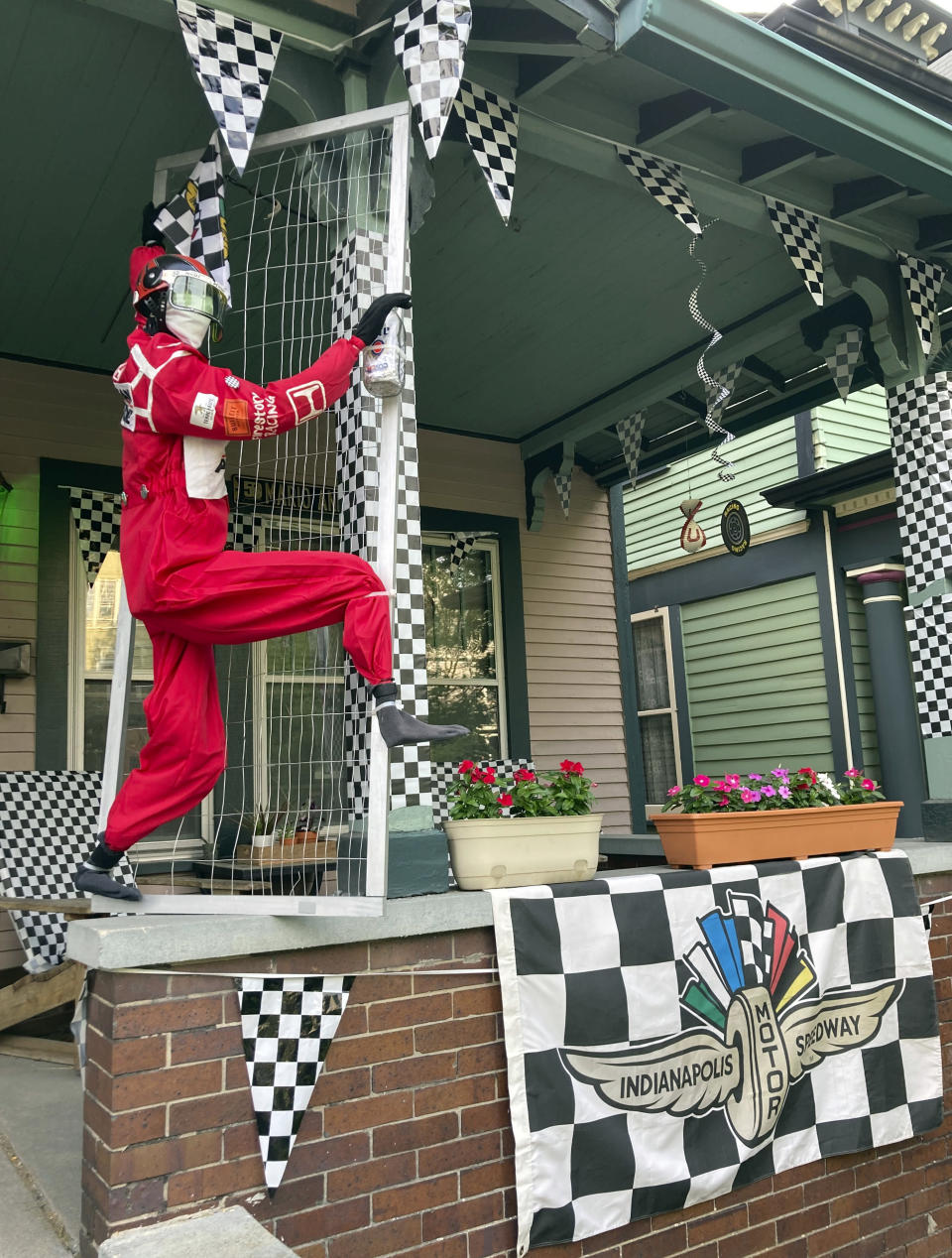 The home of Jameson and Kimmy Terzini, decorated as part of the Spectacle of Homes contest to be featured ahead of the Indianapolis 500 auto race, is shown Thursday, May 27, 2021, in Indianapolis. The husband and wife included a replica of favorite driver Helio Castroneves climbing their porch in hopes of being selected to be featured in the parade ahead of Sunday's race. (AP Photo/Jenna Fryer)