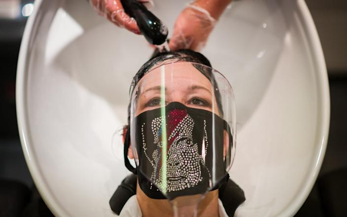 A woman has her hair washed - Getty Images Europe