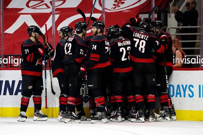 The Carolina Hurricanes celebrate with Jordan Staal after his overtime goal against the Nashville Predators in an NHL hockey game in Raleigh, N.C., Tuesday, March 9, 2021. (AP Photo/Karl B DeBlaker)