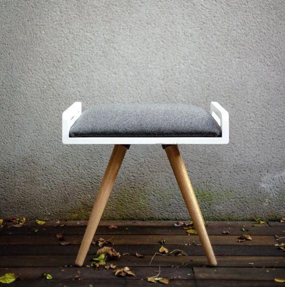 "This modern bench is made of solid oak with a wool upholstered cushion. It offers great versatility to be used as seating or an ottoman for the living room. Get it on <a href=""https://www.etsy.com/listing/214681693/new-stool-seat-ottoman-bench-in-white"" target=""_blank"">Etsy</a>."