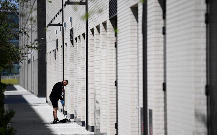 A worker cleans an empty street by newly built office buildings and commercial properties at the redeveloped Royal Albert Dock