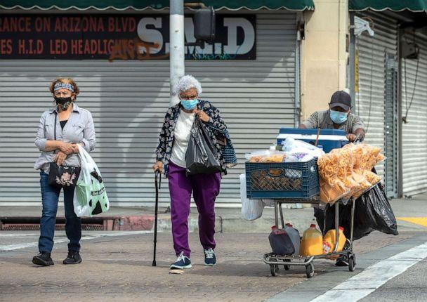 PHOTO: Pedestrians cross the street while walking along Whittier Blvd. in East Los Angeles, April 7, 2021.   (Mel Melcon/Los Angeles Times via Getty Images, FILE)