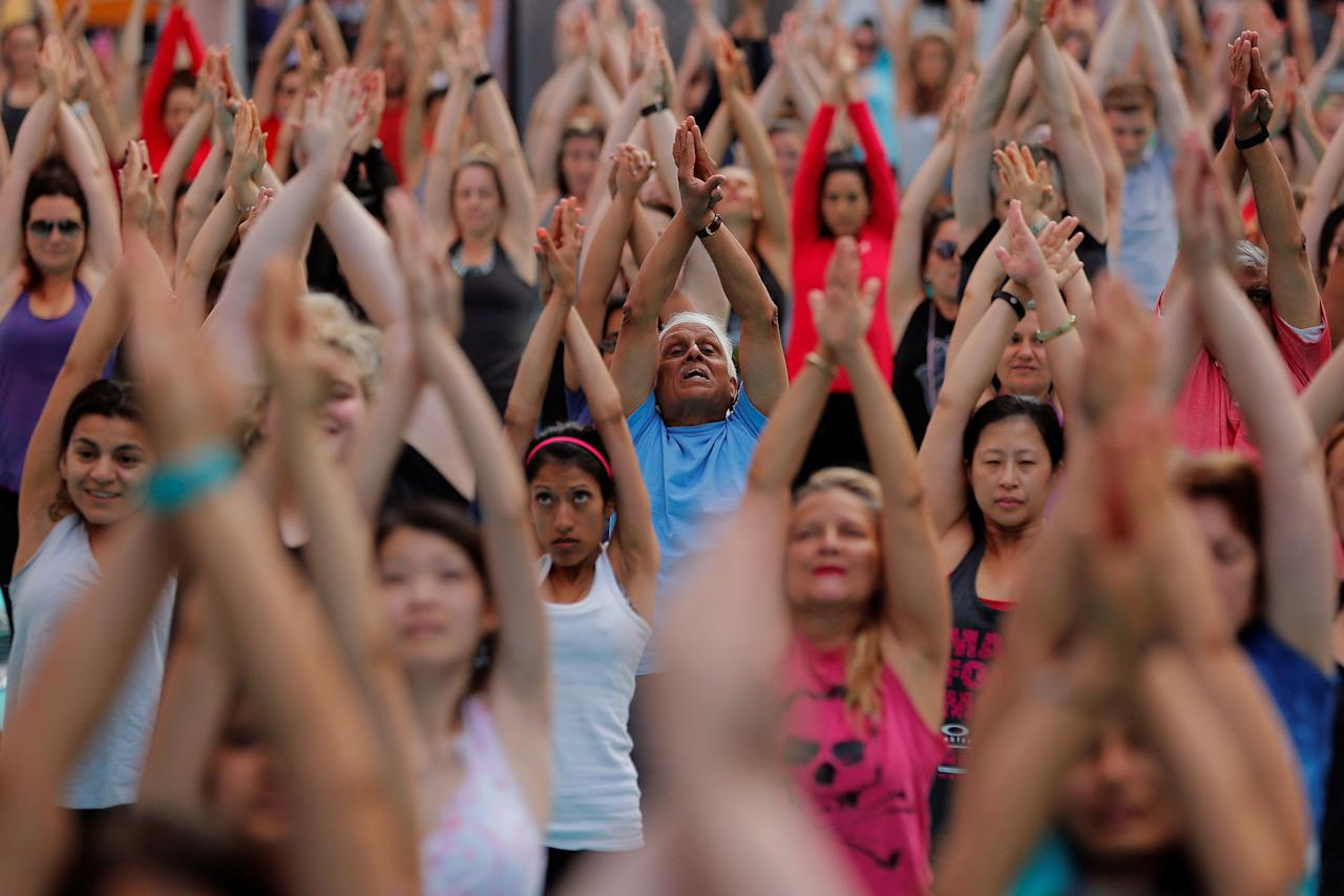 <p>People participate in a yoga class during an annual Solstice event in the Times Square district of New York, June 21, 2017. (Photo: Lucas Jackson/Reuters) </p>