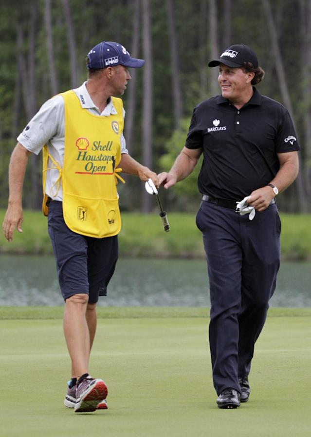 Phil Mickelson, right, smiles at his caddie Jim Mackay as he birdies on the fourth hole during the first round of the Houston Open golf tournament on Thursday, April 3, 2014, in Humble Texas. (AP Photo/Patric Schneider)