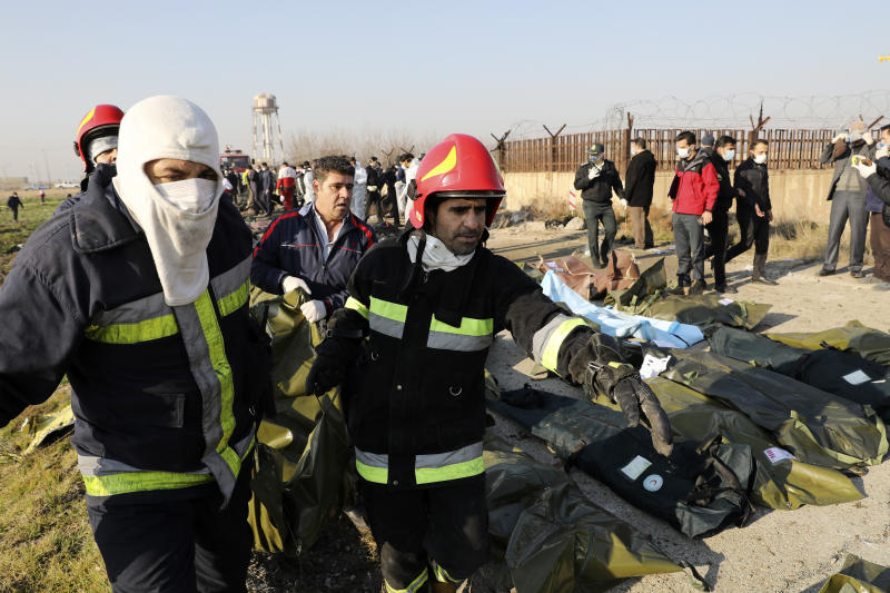 Rescue workers carry the body of a victim of an Ukrainian plane crash in Shahedshahr southwest of the capital Tehran, Iran, Wednesday, Jan. 8, 2020. (Photo: Ebrahim Noroozi/AP)