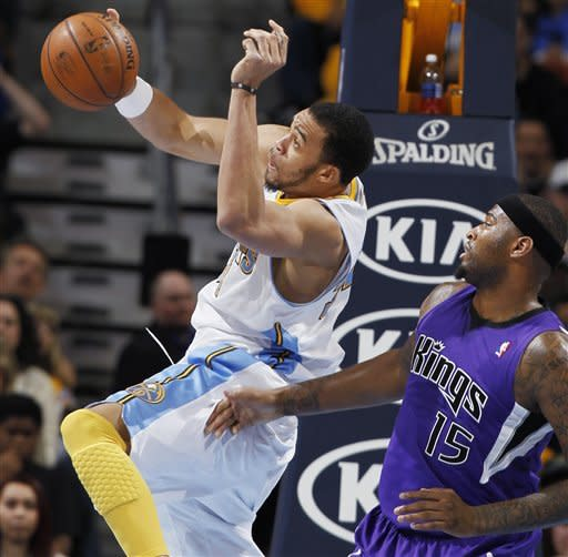 Denver Nuggets forward JaVale McGee, left, pulls in a rebound in front of Sacramento Kings center DeMarcus Cousins in the first quarter of an NBA basketball game in Denver on Saturday, March 23, 2013. (AP Photo/David Zalubowski)