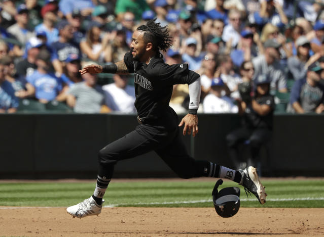 Seattle Mariners' J.P. Crawford leaves his helmet behind as he races home to score against the Toronto Blue Jays in the fourth inning of a baseball game Sunday, Aug. 25, 2019, in Seattle. (AP Photo/Elaine Thompson)