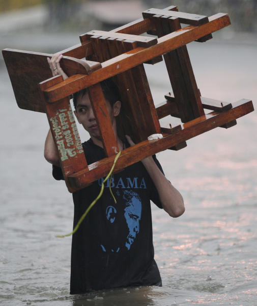 A resident wearing a shirt with a picture of US President Barack Obama carries a chair as he wades along a flooded area in Quezon City, north of Manila, Philippines, on Tuesday Aug. 7, 2012. Relentless rains submerged half of the sprawling Philippine capital, triggered a landslide that killed eight people and sent emergency crews scrambling Tuesday to rescue and evacuate tens of thousands of residents. (AP Photo/Aaron Favila)