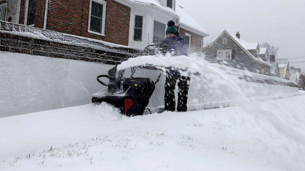 PHOTO: Doreen Goy, of Warwick, R.I., uses a snowblower to clear a sidewalk after a second round of snow struck the area, Dec. 3, 2020. (William J. Kole/AP)