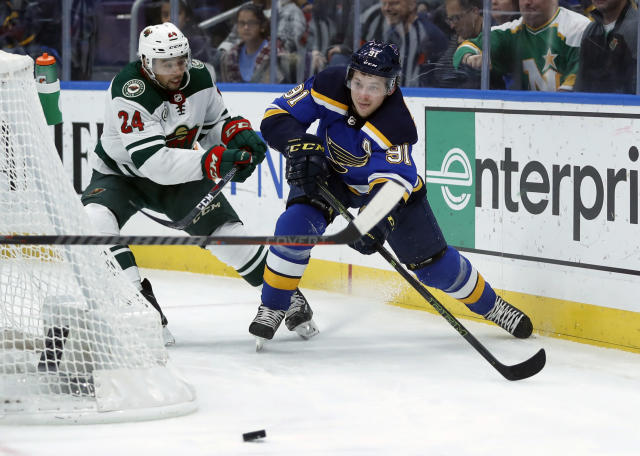 St. Louis Blues' Vladimir Tarasenko, of Russia,right, passes the puck as Minnesota Wild's Matt Dumba, left, defends during the second period of an NHL hockey game Sunday, Nov. 11, 2018, in St. Louis. (AP Photo/Jeff Roberson)