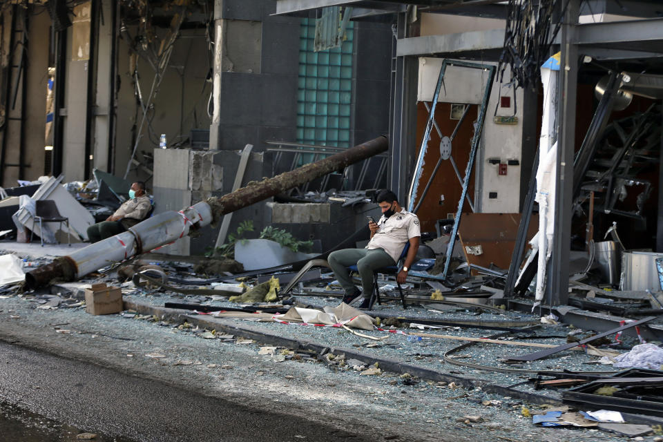 Security personnel sit in front of damaged buildings near the site of an explosion on Tuesday that hit the seaport of Beirut, Lebanon, Thursday, Aug. 6, 2020. The blast which appeared to have been caused by an accidental fire that ignited a stockpile of ammonium nitrate at the port, rippled across the Lebanese capital, killing at least 135 people, injuring more than 5,000 and causing widespread destruction. (AP Photo/Bilal Hussein)
