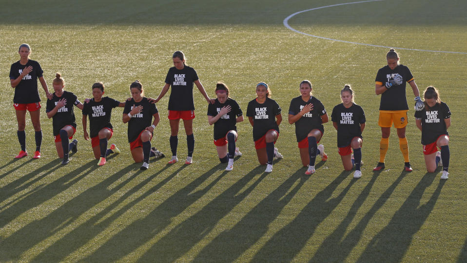 Players for the Washington Spirit kneel during the national anthem before an NWSL Challenge Cup soccer match against the Chicago Red Stars at Zions Bank Stadium, Saturday, June 27, 2020, in Herriman, Utah. (AP Photo/Rick Bowmer)