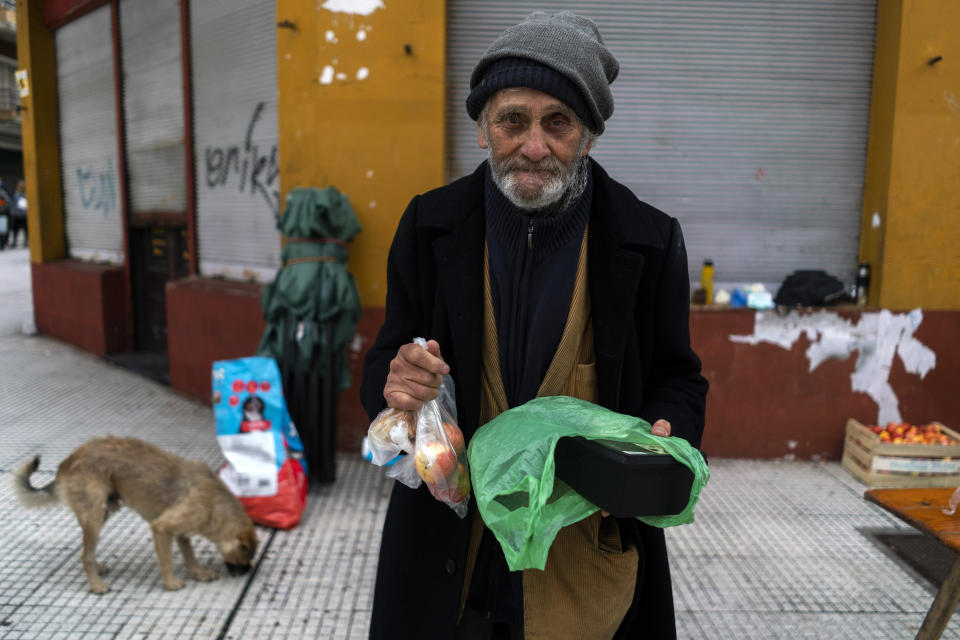 A man poses for a photo holding food he received from a group of neighbors who have formed to help people in need facing hardship amid the new coronavirus pandemic, in the financial district of Montevideo, Uruguay, Saturday, April 25, 2020. (AP Photo/Matilde Campodonico)