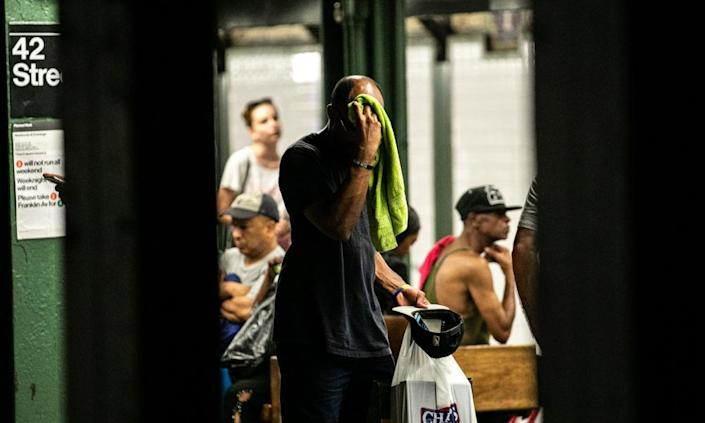 """<span class=""""element-image__caption"""">A man wipes his face with a towel while standing on subway platform in New York on 20 July 2019 amid forecasts of a heatwave.</span> <span class=""""element-image__credit"""">Photograph: Bloomberg via Getty Images</span>"""