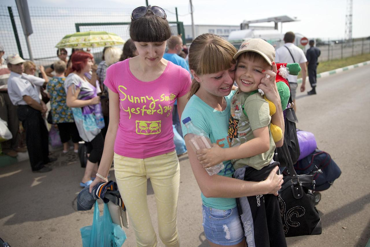 A refugee, Anastasia, centre, from the Ukrainian town of Sukhodolsk holds her four-year-old son Daniel, who is came with her friend, left, from the Ukrainian side, as white trucks of the Russian aid convoy move to the border control point with Ukraine in the Russian town of Donetsk, Rostov-on-Don region, Russia, Friday, Aug. 22, 2014. The first trucks in a Russian aid convoy crossed into eastern Ukraine on Friday, seemingly without Kiev's approval, after more than a week's delay amid suspicions the mission was being used as a cover for an invasion by Moscow. (AP Photo/Pavel Golovkin)