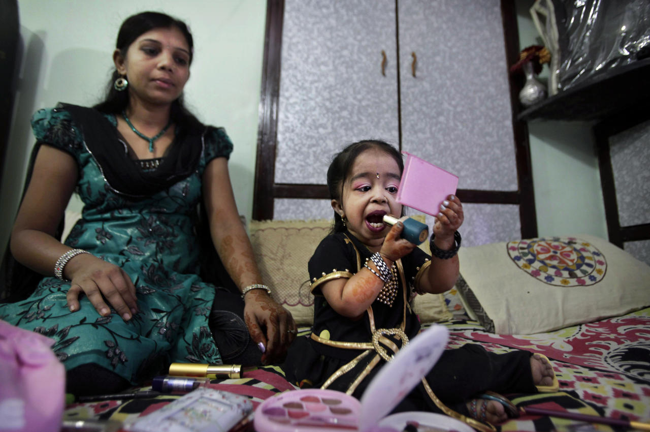 Indian Jyoti Amge, 18, who stands at 61.95 centimeters (2 feet), puts on lipstick while her sister Archna looks on as she prepares for a press conference with Guinness World Records in Nagpur, India, Friday, Dec. 16, 2011. Officials from Guinness were expected to measure Amge later Friday and declare her the World's Shortest Woman. (AP Photo/Manish Swarup)