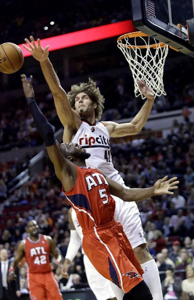 Atlanta Hawks forward DeMarre Carroll shoots against Portland Trail Blazers center Robin Lopez, top, during the first half of an NBA basketball game in Portland, Ore., Wednesday, March 5, 2014. (AP Photo/Don Ryan)