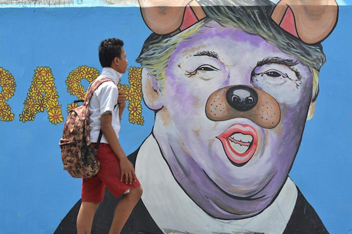 <p>A student passes in front of a mural depicting US President Donald Trump with a nose and ears like a dog at Palu on February 27, 2017 in Central Sulawei, Indonesia. (Photo: Sijori Images / Barcroft Images) </p>