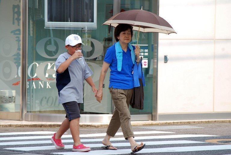 A boy and a woman shielding herself from the sun pictured in Shimanto, Japan's Kochi prefecture, August 12, 2013