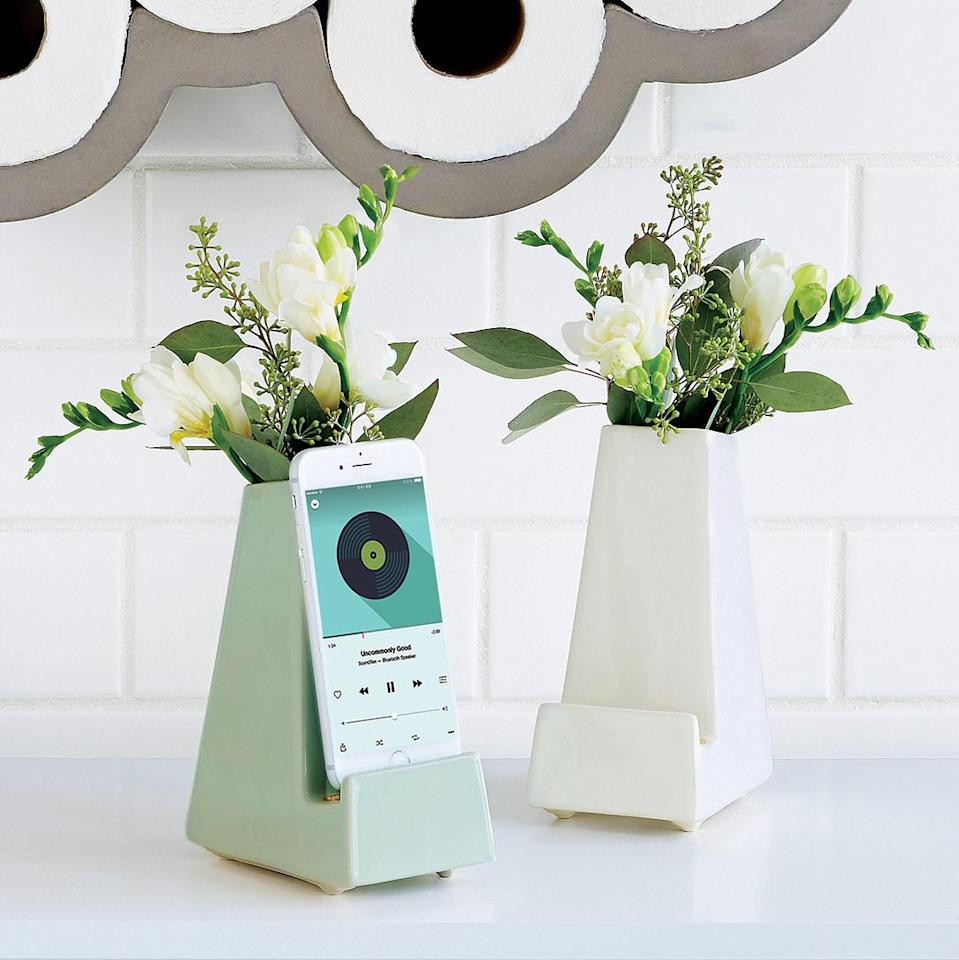 """<p>This stress-free product combines a phone dock and a flowerpot for a clever mix of practical and beautiful. It's a fun addition to any desk or room, especially for the workaholic who needs a little natural beauty to liven up her desk. </p><p>Buy it <a rel=""""nofollow noopener"""" href=""""http://click.linksynergy.com/fs-bin/click?id=93xLBvPhAeE&subid=0&offerid=458243.1&type=10&tmpid=319&RD_PARM1=http%253A%252F%252Fwww.uncommongoods.com%252Fproduct%252Fbedside-smartphone-vase&u1=ISSPWORKAHOLICGIFTGUIDE"""" target=""""_blank"""" data-ylk=""""slk:here"""" class=""""link rapid-noclick-resp"""">here</a> for $32.</p>"""