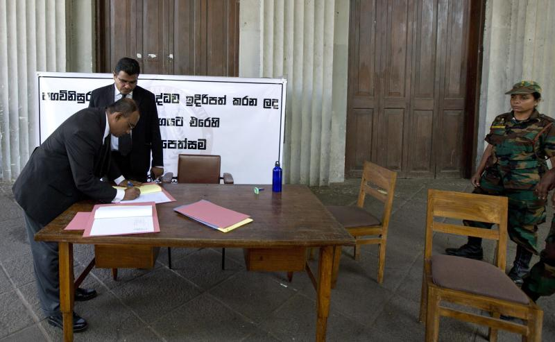 FILE - In this Wednesday, Nov. 7, 2012 file photo, a Sri Lankan lawyer signs a petition requesting the United Nations and the International Bar Association to send observers to monitor Parliament's handling of an impeachment complaint against Chief Justice Shirani Bandaranayake in Colombo, Sri Lanka. When Shirani Bandaranayake was appointed Sri Lanka's chief justice, rights campaigners assailed her as a puppet of a government that was steamrolling opponents and consolidating power. (AP Photo/Gemunu Amarasinghe, File)