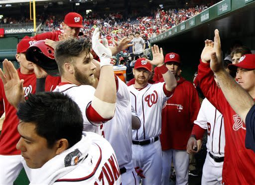 Washington Nationals' Bryce Harper, left, celebrates his two-run homer with his teammates during the first inning of a baseball game against the Atlanta Braves at Nationals Park, Friday, April 12, 2013, in Washington. (AP Photo/Alex Brandon)