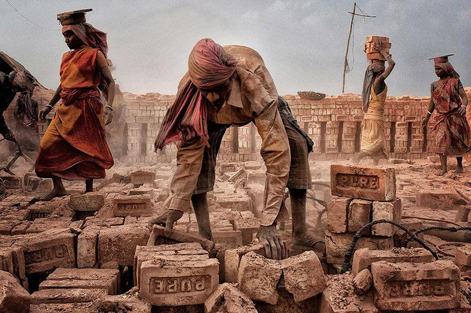 <p>Men and women work alongside one another in West Bengal, India, lifting heavy bricks for construction. (Shibasish Saha) </p>
