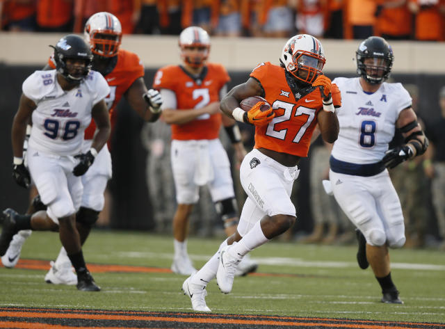 Oklahoma State running back J.D. King (27) breaks through the line and runs past Tulsa's Jeremy Smith (98) and Jesse Brubaker (8) for a 71-yard touchdown during the first half of an NCAA college football game against Tulsa in Stillwater, Okla., Thursday, Aug. 31, 2017. (AP Photo/Sue Ogrocki)