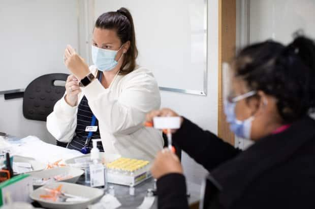 The Pfizer vaccine is administered at a Fraser Health and City of Surrey community clinic in Bear Creek Park in Surrey, B.C., on Monday, May 17, 2021. Epidemiologists have said that at least 60 to 70 per cent of the total population must be immunized in order to achieve herd immunity.