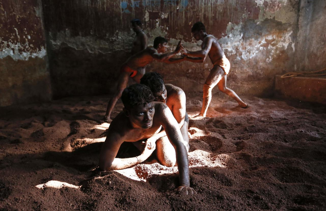 Wrestlers practise in the mud at a traditional Indian wrestling centre called Akhaara in Mumbai March 4, 2014. Kushti (mud wrestling) is a traditional sport in India but more and more young athletes are now training to wrestle on mats instead of mud to gain access to top international competitions like the Olympic Games or the Commonwealth Games. REUTERS/Danish Siddiqui (INDIA - Tags: SOCIETY SPORT)