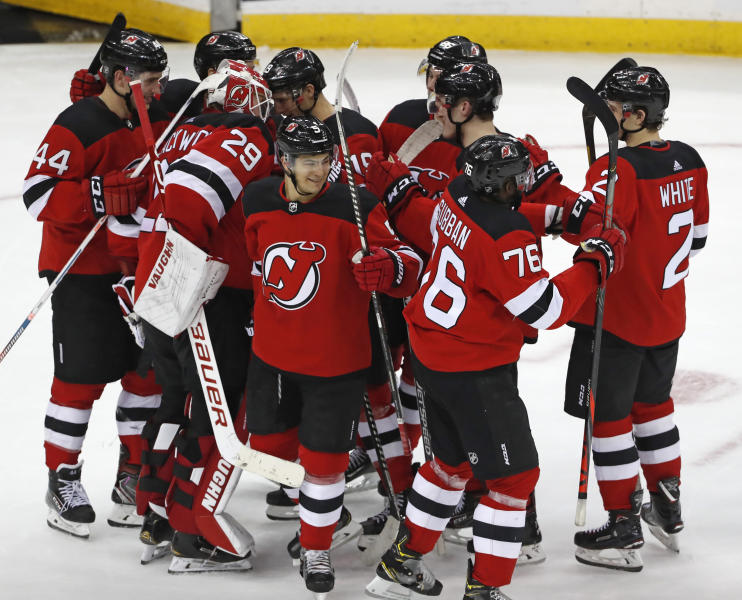 New Jersey Devils players celebrate after defeating the Columbus Blue Jackets 4-3 in a shootout in an NHL hockey game, Sunday, Feb. 16, 2020, in Newark, N.J.  (AP Photo/Kathy Willens)