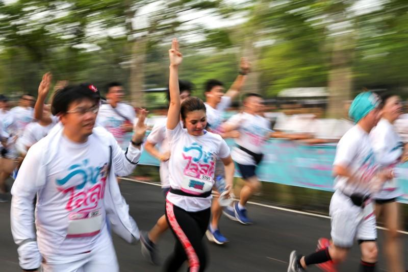 """Runners flash the three-finger salute as they attend the """"Run Against Dictatorship"""" event at a Public park in Bangkok"""
