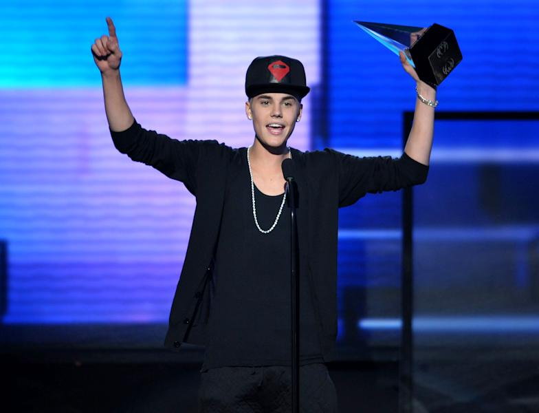 """FILE - In this Nov. 18, 2012 file photo, Justin Bieber accepts the award for favorite album - pop/rock for """"Believe"""" at the 40th Anniversary American Music Awards, in Los Angeles. Los Angeles police announced Tuesday Dec. 18, 2012 that they have arrested an unidentified juvenile for sending hoax messages that led to large police responses to the homes of Ashton Kutcher and Justin Bieber. (Photo by John Shearer/Invision/AP, File)"""