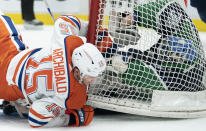 Edmonton Oilers right wing Josh Archibald (15) crashes into Vancouver Canucks goaltender Thatcher Demko (35) and the goal during the first period of an NHL hockey game Thursday, Feb. 25, 2021, in Vancouver, British Columbia. (Jonathan Hayward/The Canadian Press via AP)