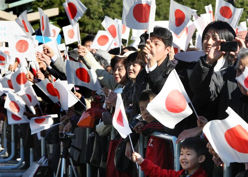 Well-wishers wave Japanese flags as Japan's Emperor Akihito makes a public appearance marking his 77th birthday at the Imperial Palace in Tokyo Thursday, Dec. 23, 2010.