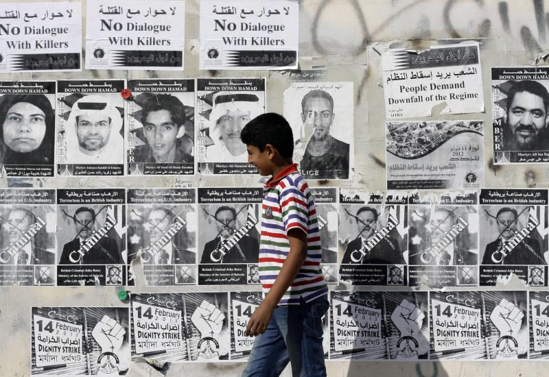 A Bahraini boy walks by a wall with signs in English and Arabic objecting to a government-mediated dialogue scheduled for Sunday between opponents  and supporters of the Bahraini monarchy in Sitra, Bahrain, on Saturday, Feb. 9, 2013. Bilingual posters on the wall are honoring those who have died in recent unrest, condemning U.S. President Barak Obama and British Prime Minister David Cameron, and promoting the street demonstration plans of the Feb. 14 youth group on the upcoming second anniversary of Bahrain's pro-democracy uprising. (AP Photo/Hasan Jamali)