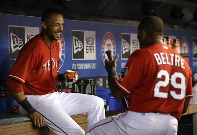 Texas Rangers' Alex Rios, left, talks with Adrian Beltre (29) in the dugout after Rios scored on a sacrifice fly by Beltre against the Houston Astros in the sixth inning of a baseball game, Monday, Sept. 23, 2013, in Arlington, Texas. Rios hit for the cycle. (AP Photo/Tony Gutierrez)