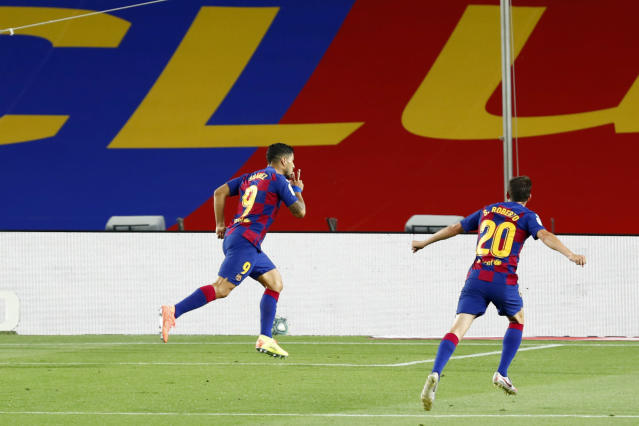 Barcelona's Luis Suarez celebrates scoring the opening goal during the Spanish La Liga soccer match between FC Barcelona and RCD Espanyol at the Camp Nou stadium in Barcelona, Spain, Wednesday, July 8, 2020. (AP Photo/Joan Monfort)