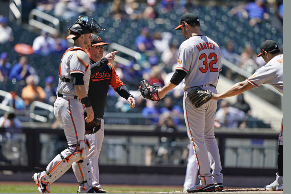 Baltimore Orioles manager Brandon Hyde points to the bullpen as he comes to take Orioles starting pitcher Matt Harvey (32) from the mound during the fifth inning of a baseball game against the New York Mets, Wednesday, May 12, 2021, in New York. (AP Photo/Kathy Willens)