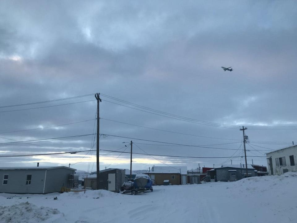 A town in a snowy landscape with a plane flying overhead.