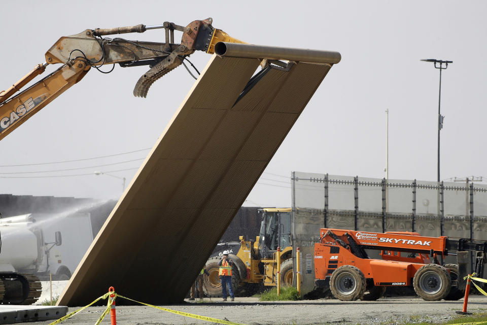 In this Feb. 27, 2019, file photo, a border wall prototype falls during demolition at the border between Tijuana, Mexico, and San Diego. The government is demolishing eight prototypes of Donald Trump's prized border wall that instantly became powerful symbols of his presidency when they were built nine months after he took office. The Biden administration says it will begin work to address flooding and soil erosion risks from unfinished walls on the U.S. border with Mexico. It also began providing answers on how it will use unspent money from shutting down one of President Donald Trump's signature domestic projects. The Defense Department says it will use unobligated money for military construction projects for its initial purpose. (AP Photo/Gregory Bull, File)