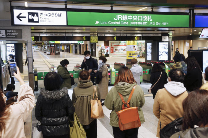 People gather in front of a ticket gate at a station as train services are suspended following an earthquake in Sendai, Miyagi prefecture, Japan Saturday, March 20, 2021. A strong earthquake struck Saturday off northern Japan, shaking buildings even in Tokyo and triggering a tsunami advisory for a part of the northern coast. (Kyodo News via AP)