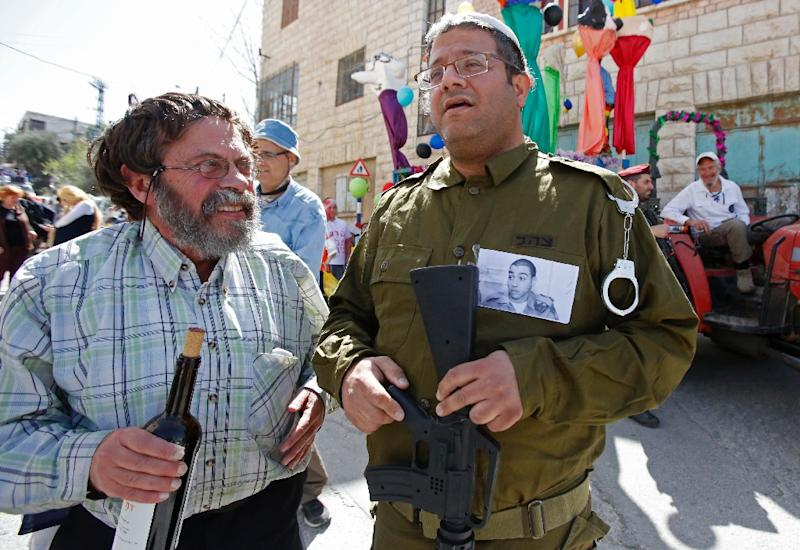 A Jewish settler dressed in military fatigues wears a portrait of Elor Azaria, an Israeli soldier who shot dead a wounded Palestinian assailant, during a parade marking the Jewish holiday of Purim in Hebron on March 12, 2017 (AFP Photo/HAZEM BADER)