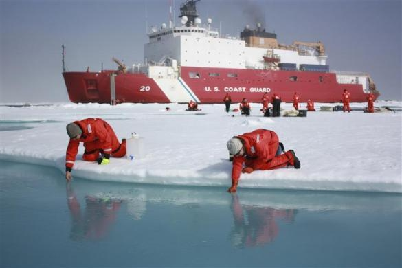 Scientists Jens Ehn (L) and Christie Wood scoop water from melt ponds on sea ice in the Chukchi Sea in the Arctic Ocean in this July 10, 2011 NASA handout photo obtained by Reuters June 10, 2012.