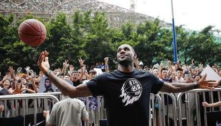 LeBron James plays with a basketball during a promotional event at a store in Guangzhou