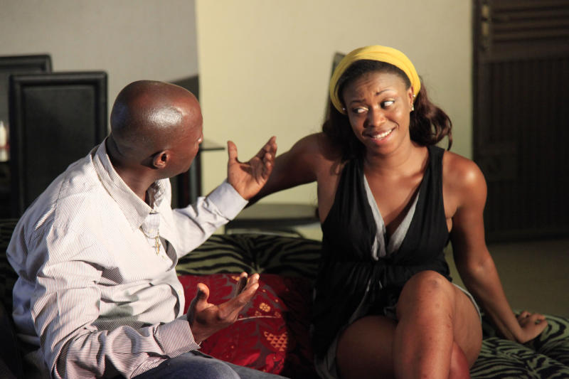 """In this photo taken Wednesday, Sept, 18. 2013, Nollywood sctors perform a scene in Lagos, Nigeria. A 15-second drum roll and the title of the film, """"Deceptive Heart,"""" comes crashing onto the screen in a groovy 1970s font. Less than 10 minutes into the Nollywood movie, the heart of plot is revealed: A woman has two boyfriends and doesn't know what to do. The story moves as quickly as the film appears to have been shot. Some scenes are shaky, with cameras clearly in need of a tripod, and musical montages are often filled with pans of the same building. Most Nollywood movies are made in less than 10 days and cost about $25,000. (AP Photo/ Sunday Alamba)"""