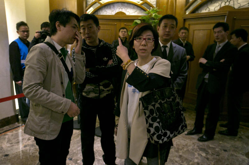 Relatives of Chinese passengers aboard the missing Malaysia Airlines flight MH370 at left and right speak with a person in charge of security to give journalists access to a meeting in Beijing, China, Monday, March 24, 2014. Rain was expected to hamper the hunt Monday for debris suspected of being from the missing Malaysia Airlines jet, as the United States prepared to move a specialized device that can locate black boxes into the south Indian Ocean region. (AP Photo/Ng Han Guan)